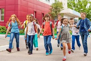 Happy kids with rucksacks walking holding hands